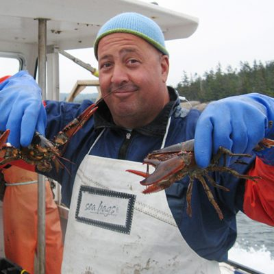 Andrew Zimmern holding a lobster.